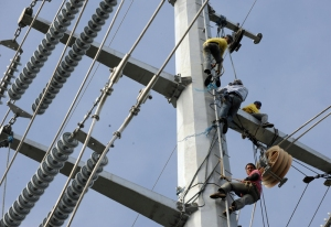 Linemen install cables on the Transco po