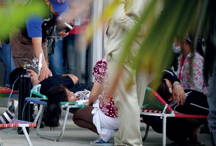 """Pracownicy dochodzą do siebie po masowych omdleniach w fabryce tekstyliów Hung Wah w Phnom Penh, 25 lipca 2011. Zemdlało ok. 100 pracowników. Przyczyna nagłego zachorowania jest nieznana. © REUTERS/Samrang  Fot. z raportu """"Brudny zysk. Jak korporacje, banki i fundusze inwestycyjne czerpią zyski z łamania praw człowieka"""""""