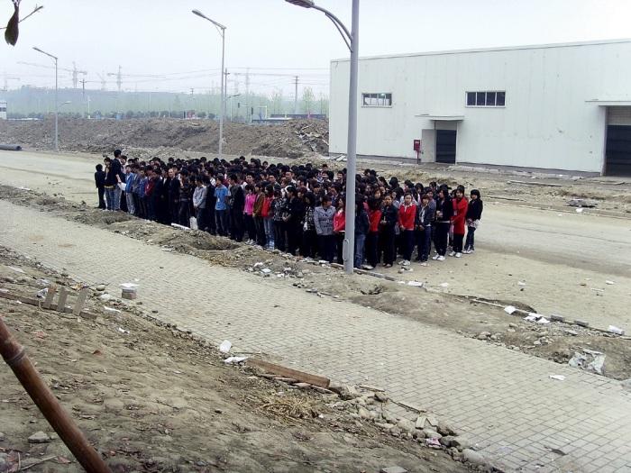 """Zdjęcie zrobione w fabryce Foxconn w Chengdu. Nowi pracownicy podczas """"treningu wojskowego"""" – całodziennego stania i musztry organizowanej przez przełożonych. © SACOM, 2011"""